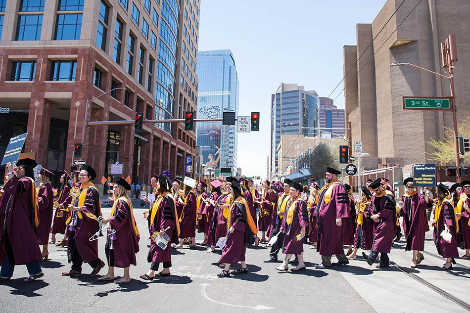 A large group of ASU graduates walking down 3rd Street