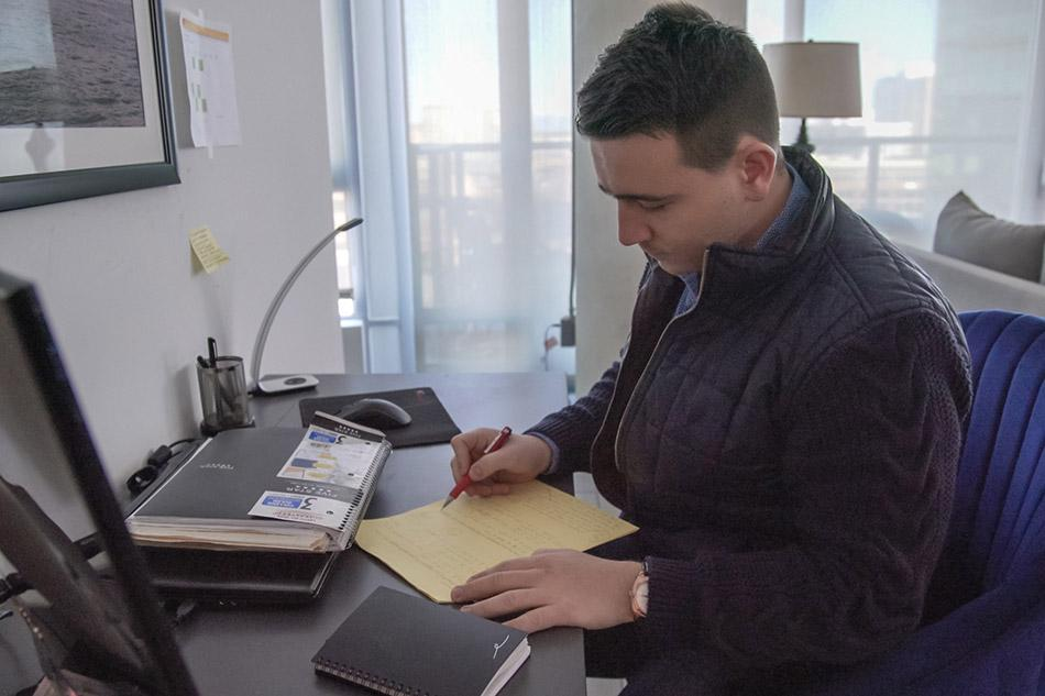 A man sitting at a desk filling out a piece of paper